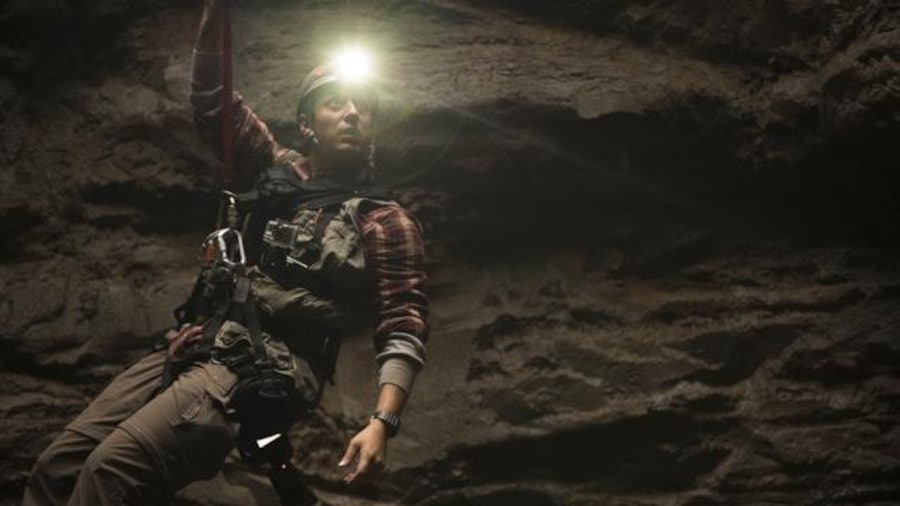 Samyan, in his role as a young archaeologist, is suspended in a huge crater by a belt lit by a headlamp.