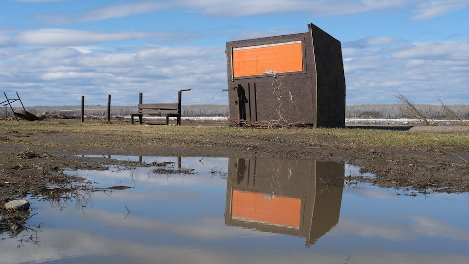 A room with an orange door on its side and reflected in a pool of water.