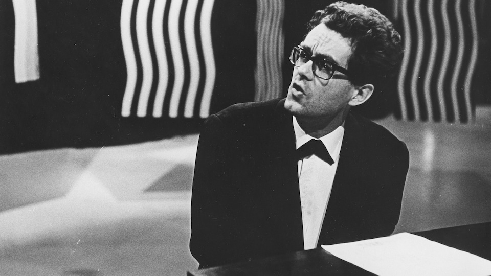 Michel Legrand singing and playing the piano in front of a bright place in 1965.