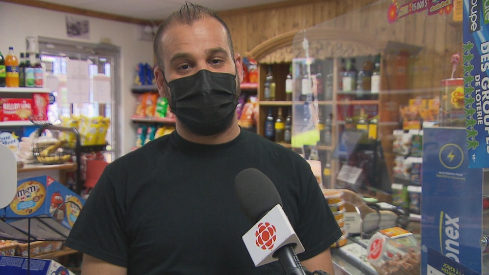 Masked man talking in a grocery store.