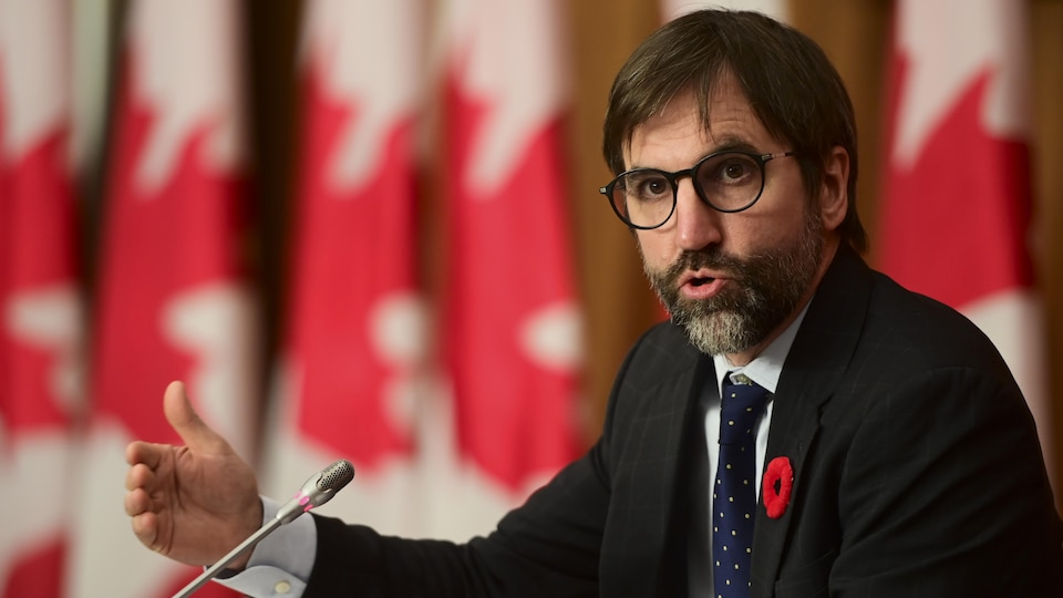 Stephen Gilbault speaking into a microphone.  And behind him several Canadian flags.