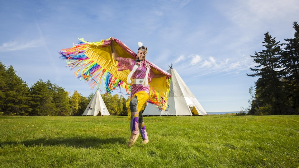 Young indigenous woman dances in traditional costume.