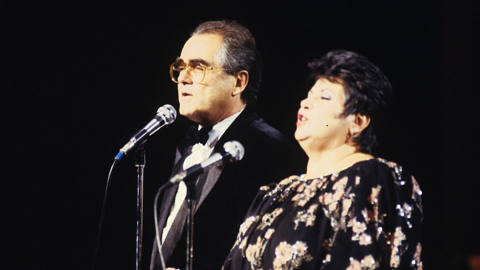 On stage at Salle Wilfrid-Pelletier at Place des Arts in Montreal, Michel Legrand and Ginette Reno sing a duet.