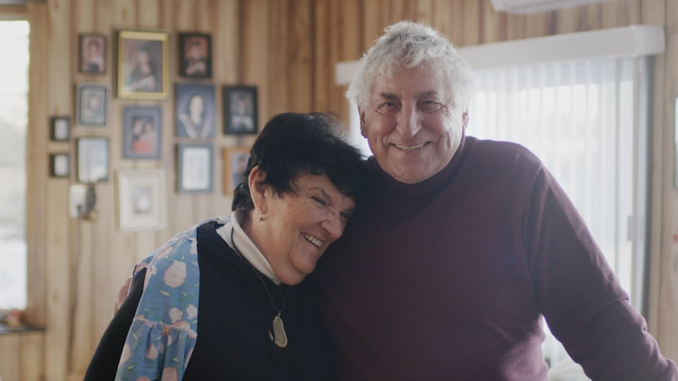 The elderly couple are glued together and standing inside.  Behind them are pictures on the wall.