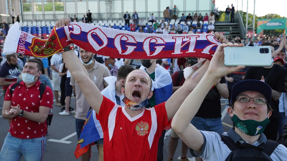 A supporter cheers and raises a banner in the colors of Russia.