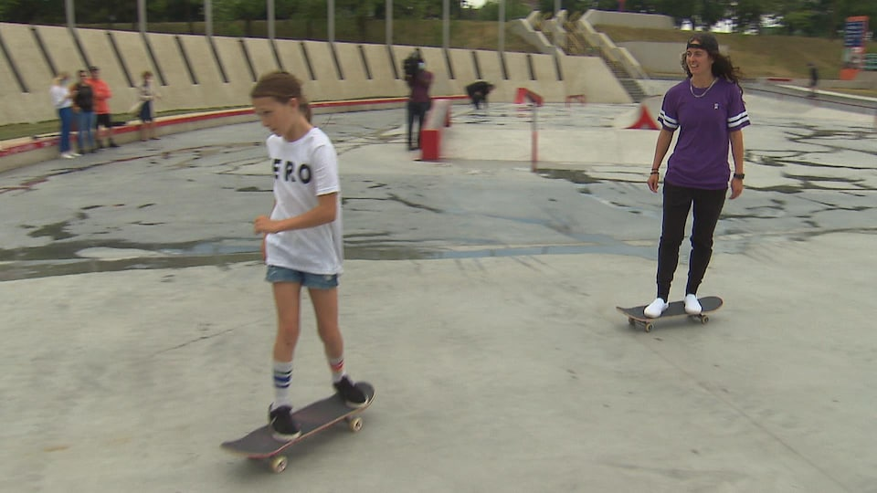 Two young women skateboarding.
