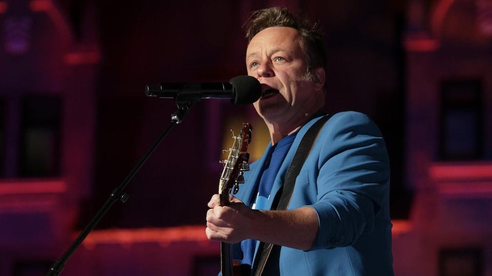 Daniel Boucher, guitar in hand, sings.