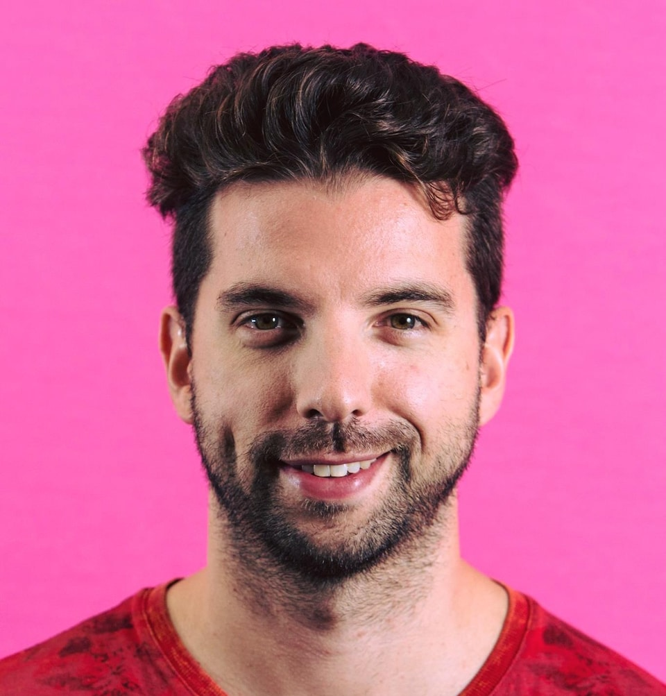 A man standing in front of a pink background.  He is brown and has a light beard.  smiling.