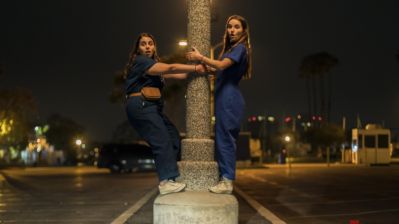 Two little girls cling to a lamppost.