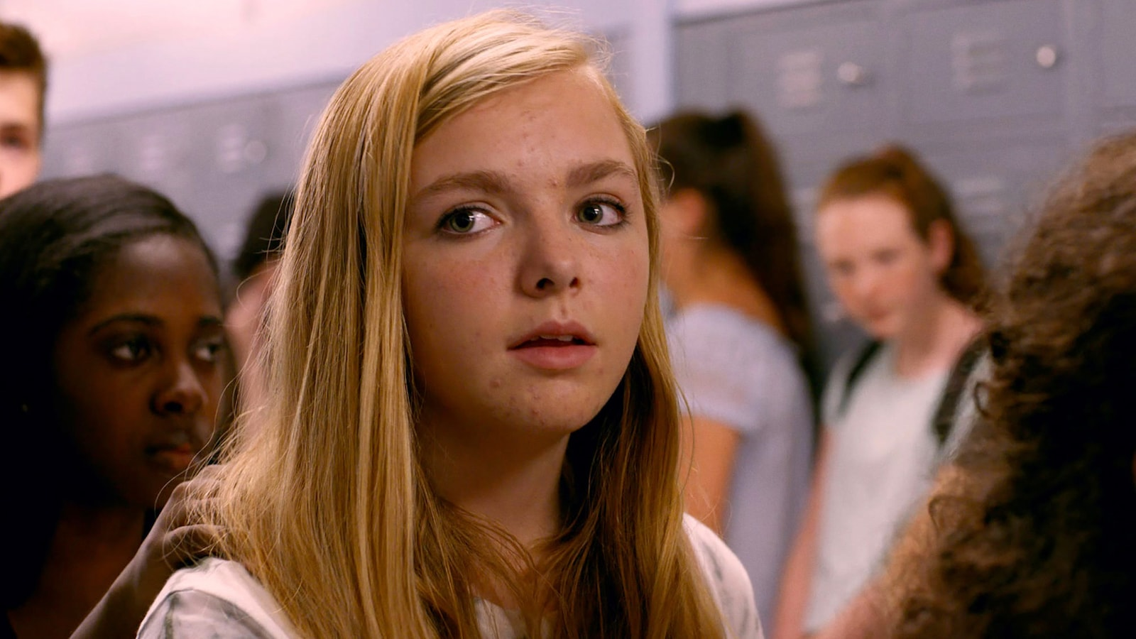 Close-up of young blonde actress Elsie Fisher in the high school hallway.