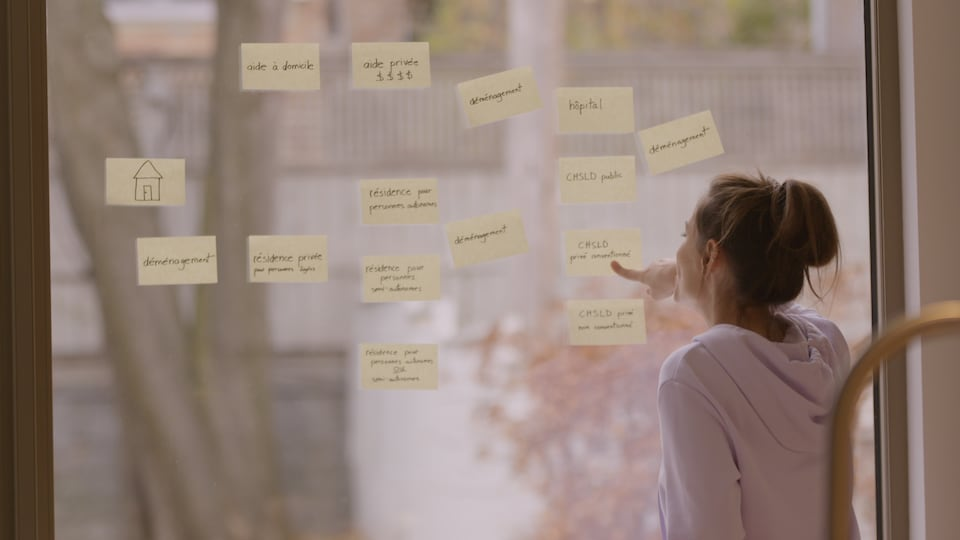 The host looks at the sticky notes on a large window.