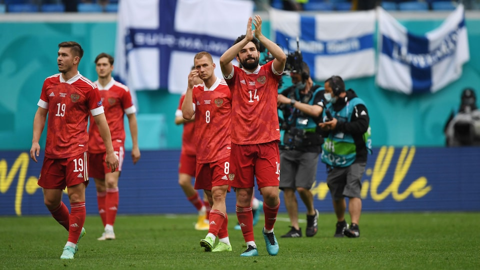 On the field, a Russian player applauds for the fans along with his teammates.