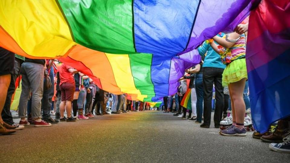People carry a rainbow flag.