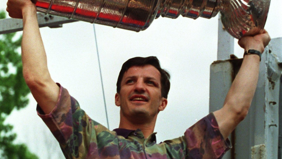 Montreal Canadiens captain Guy Carboneau lifts the Stanley Cup during the parade on June 11, 1993.