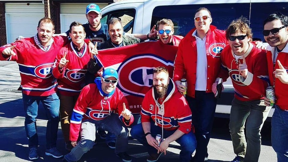Jean-Bernard Marchand (1st row, 5th left), and his friends pose for a photo in front of their truck.