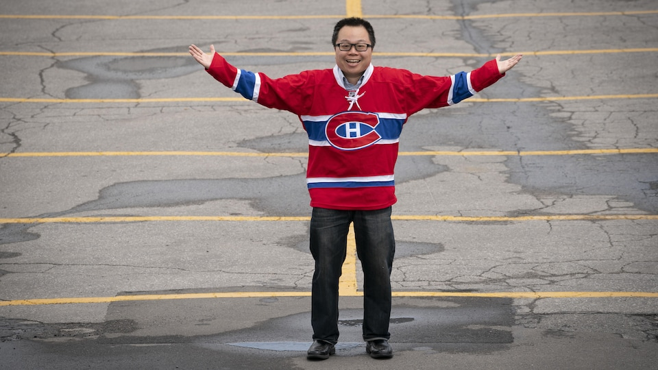 Winston Chan, in a Canadian T-shirt, raises his arms in the air in the middle of an empty parking lot.
