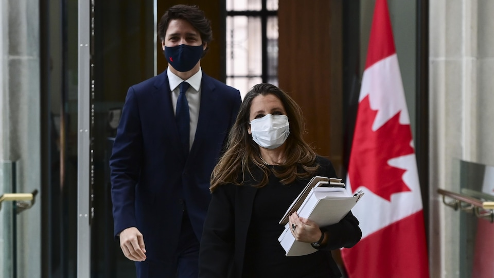 Chrystia Freeland, masked, holding documents, walks in and Justin Trudeau, also masked, follows suit.