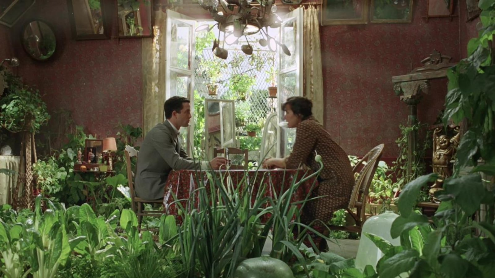 A man and a woman sitting around a table in an apartment filled with green plants.