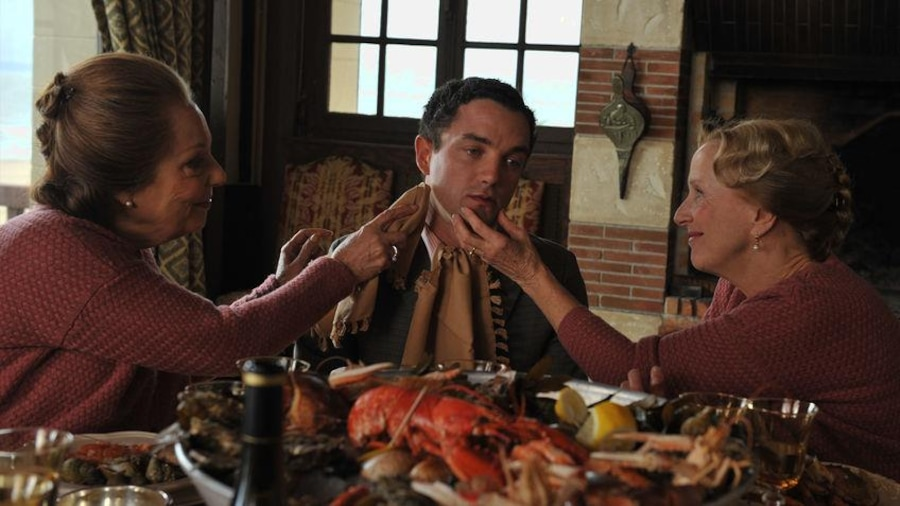 Around a table, two identically dressed women touch the face of a young man.
