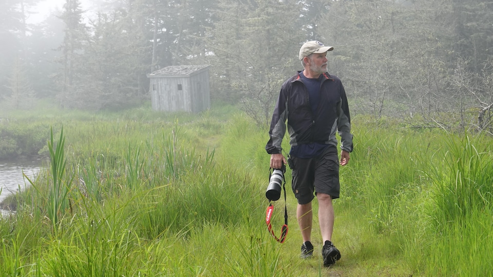A man is walking on a road near a body of water with a camera in his hand.  Behind him is a hideout for bird watching.
