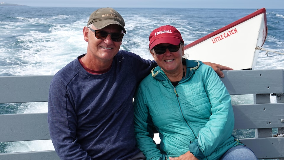 On the back seat of the boat, Claude Lepage is embracing his wife.  Behind them is a rowboat.
