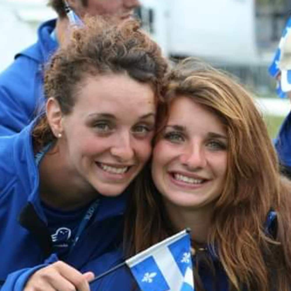Two women looking at the camera holding the Quebec flag.