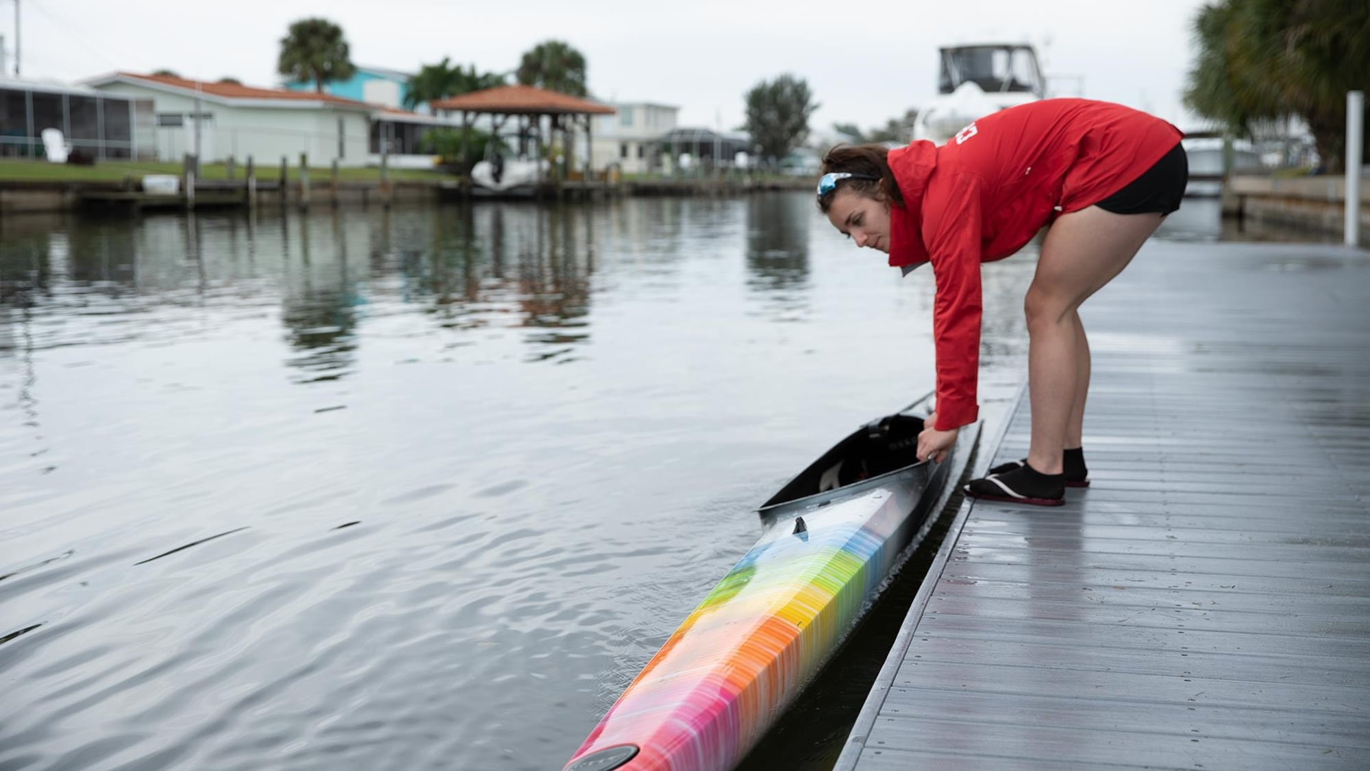 A woman lays her kayak on a body of water next to a pier.