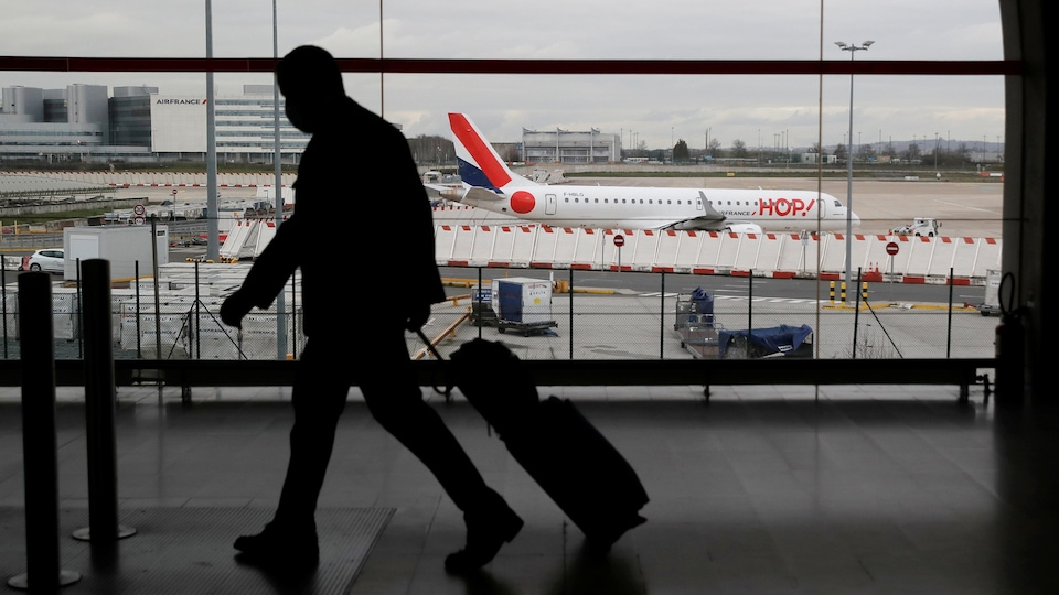 The silhouette of a man pulling a suitcase looms in front of a picture window overlooking the tarmac.