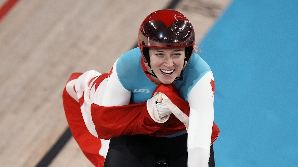 A cyclist on her bike smiling with the Canadian flag.