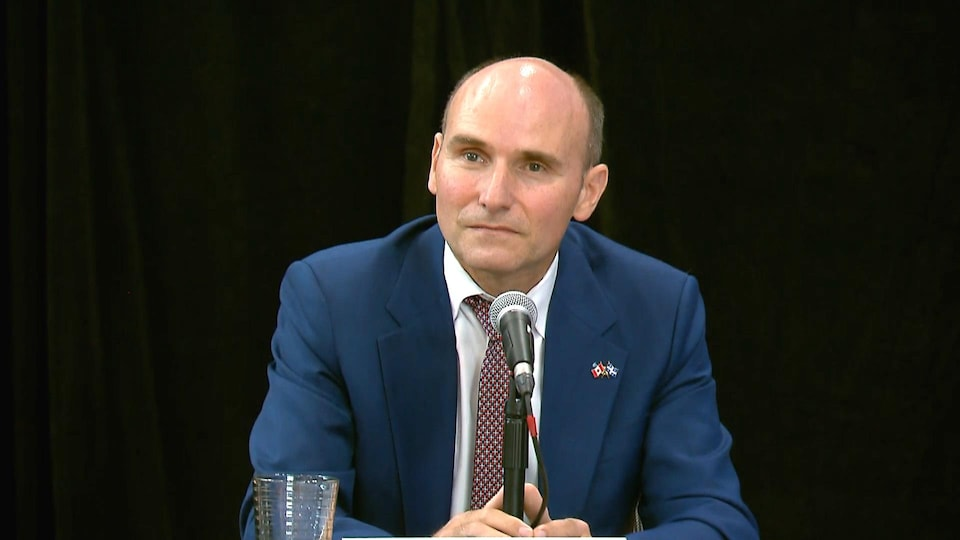Jean-Yves Duclos in front of a microphone and a black curtain in the background.