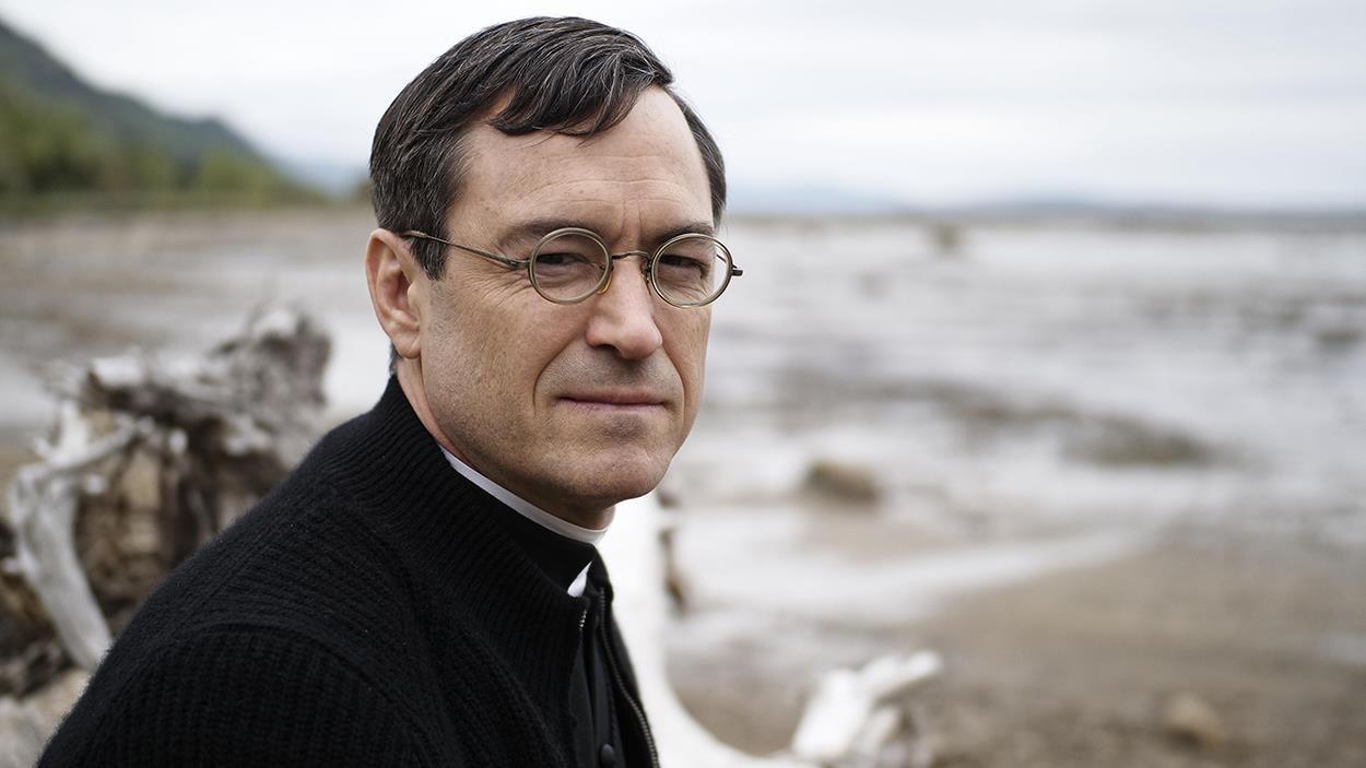 A man (Sebastian Ricard) dressed as a priest on the beach.
