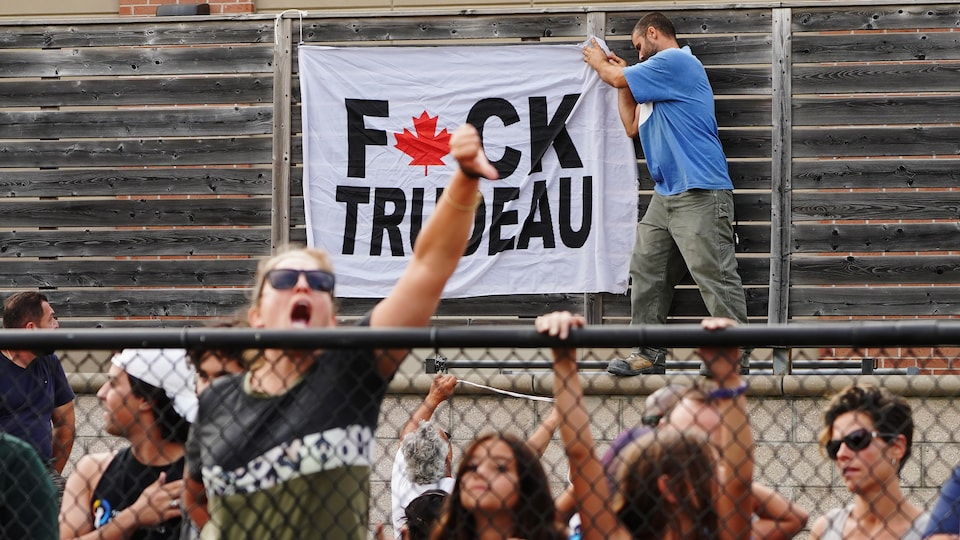 People are screaming from behind the fence.  A protester hangs an insulting note dedicated to Justin Trudeau.