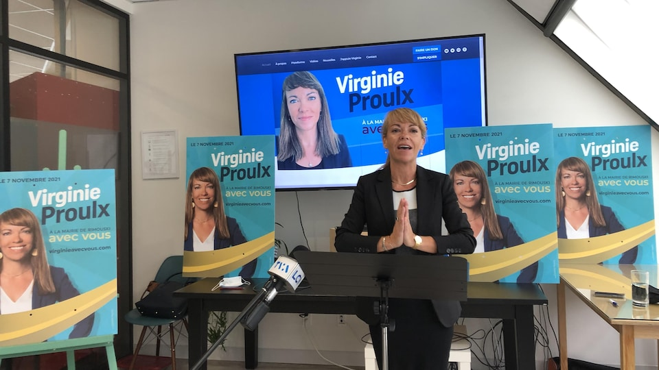 Virginie Proulx at a press conference, around which many electoral banners.