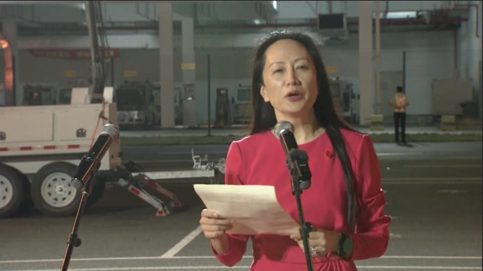 Meng Wanzhou speaking and holding a paper.