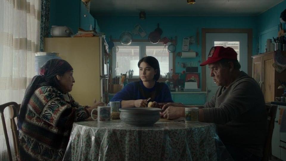 Young woman peeling potatoes between two elderly people.