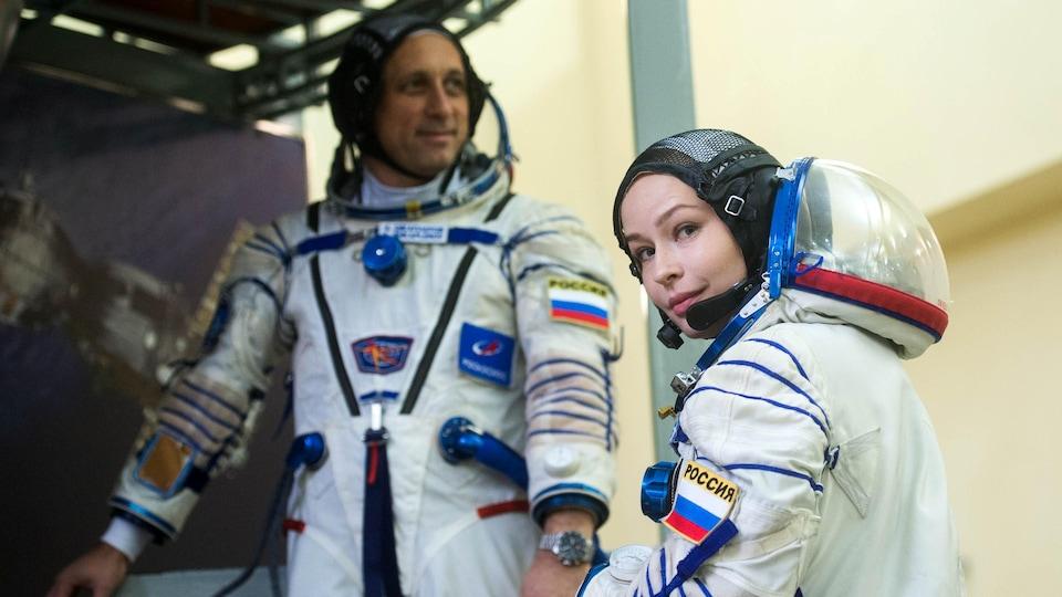 Yulia Peresild and Anton Shkaplerov put on their suits and walk.