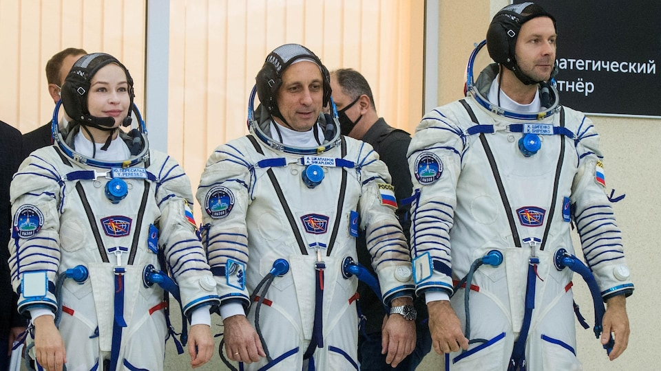 The three wear astronaut suits and stand straight.