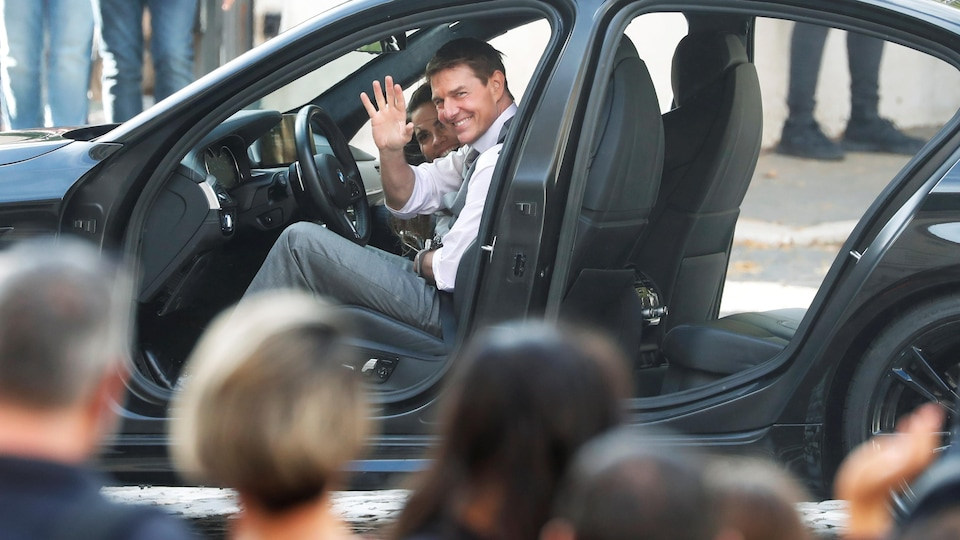 Tom Cruise in a car waving to fans.