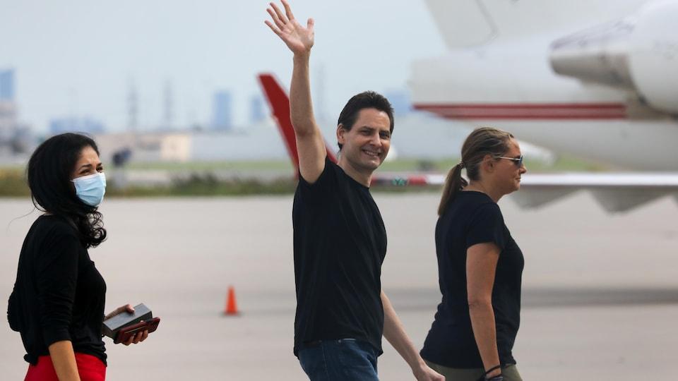 Michael Kovrig walking and waving his right hand at people.